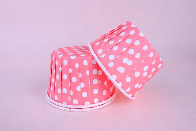 Pink polka dot paper cupcake liner, bakery background