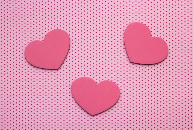 Pink polka dots background and hearts from wood