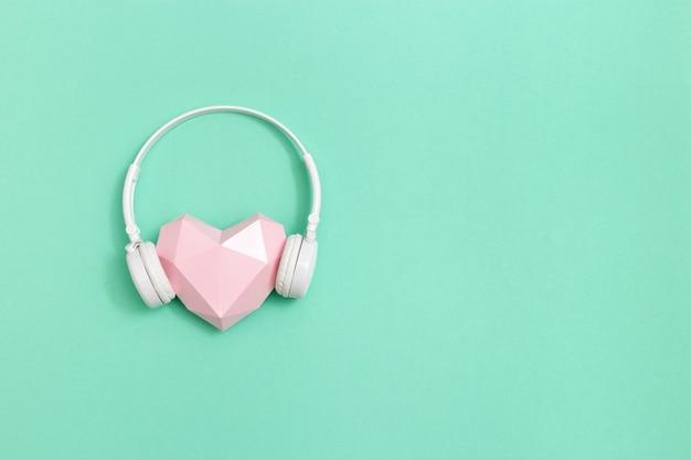 Розовая многоугольная бумажная форма сердца в белых наушниках. музыкальная концепция.