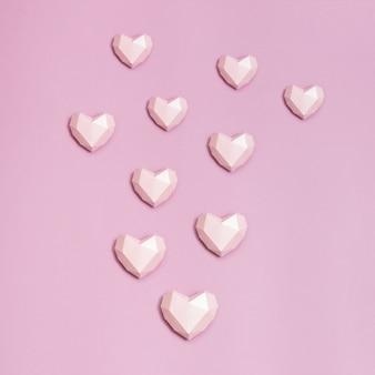 ピンクの紙にピンクの多角形紙ハート。バレンタインデーのコピースペースを持つ休日の背景。愛の概念。