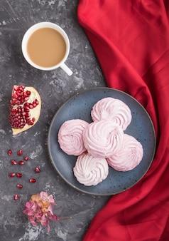 Домашний зефир или зефир из розового граната с чашкой кофе на черной бетонной поверхности с красной тканью