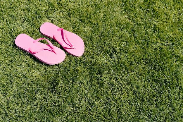 Розовые шлепанцы для бассейна на зеленой траве фон концепция лета и путешествия копией пространства