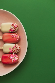 Pink popsicle cakes on a green background