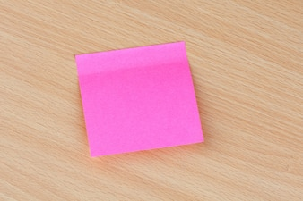 Pink Post-it stuck on a wooden surface