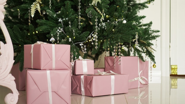 Pink present boxes with ribbons under the christmas tree in classic apartments with white interior