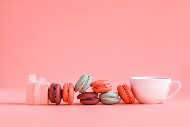 Pink present and row of french colorful macaroons and cup of coffee
