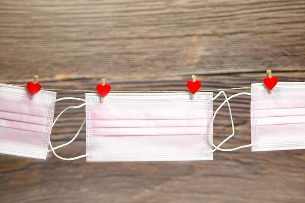 ピンクの保護医療マスクは、木製の背景に分離されたハートの形の洗濯バサミでぶら下がっています。