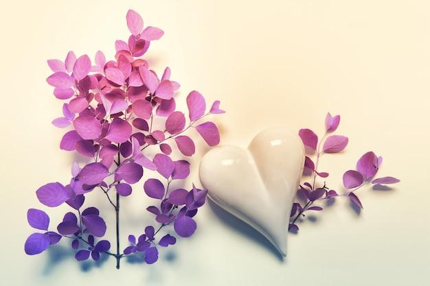 Розовый фиолетовый цвет лежал с сердцем и веткой растения
