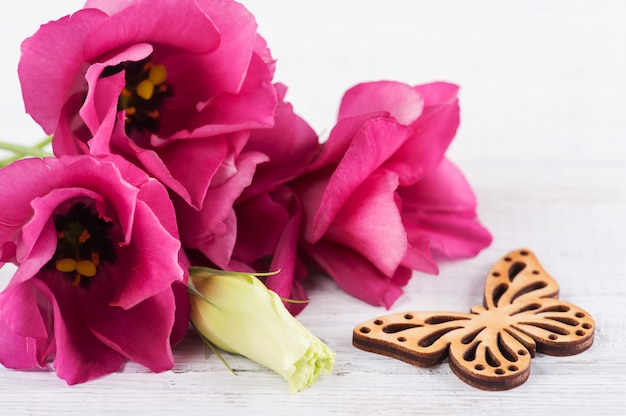 Pink purple eustoma flowers and wooden butterfly