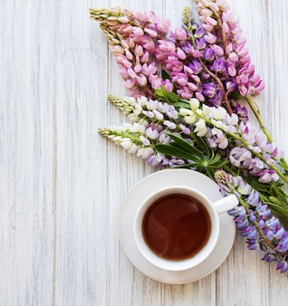 Pink and purple lupine flowers and cup of tea
