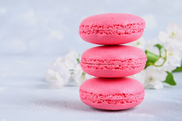 Pink and purple macaroons on a gray table surrounded by pink and white flowers.
