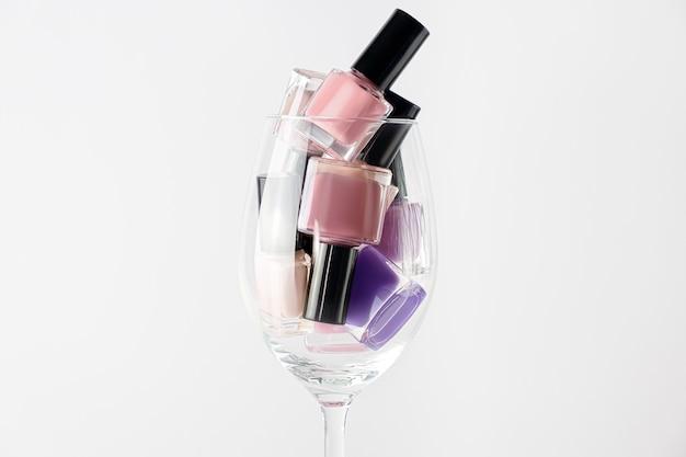 ピンク、紫のマニキュアボトルが白い表面にセットされています。