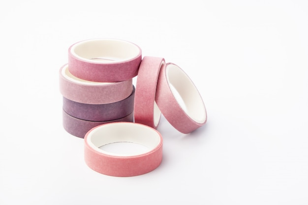 Pink and purple rolls of washi tape on a white