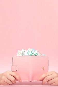 Розовый кошелек и банкноты евро в женских руках на розовом