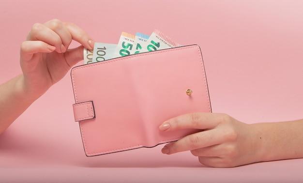 Розовый кошелек и банкноты евро в женских руках