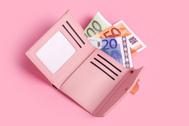 Розовый кошелек на пастельно-розовом фоне с купюрами в нем