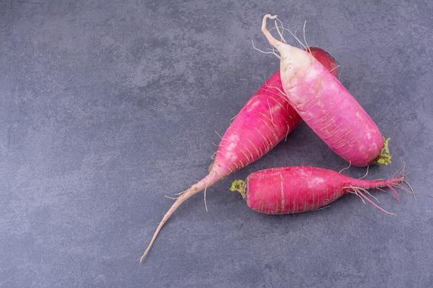Pink radish isolated on blue surface Free Photo