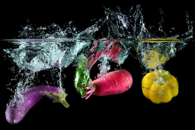 Pink radishs and other vegetables with splash water