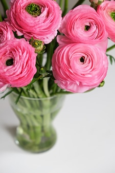 Pink ranunculus bouquet in transparent glass vase on white table.
