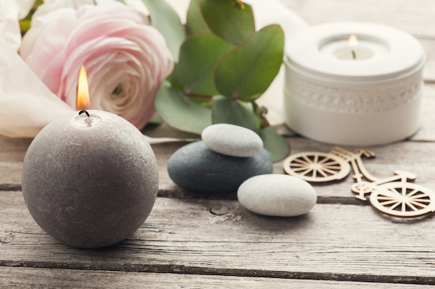 Pink ranunculus, pebbles and lit candles
