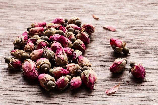 ピンクの赤い乾燥したバラのつぼみハートcopyspaceで古い木製のテーブルの上。