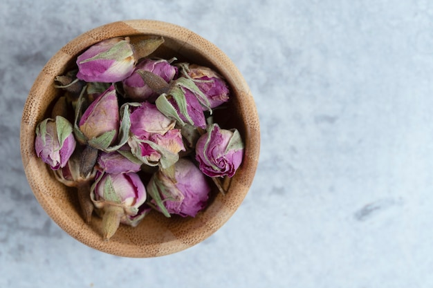 Розовые красные сушеные бутоны роз в деревянной миске с лепестками на каменном фоне. фото высокого качества