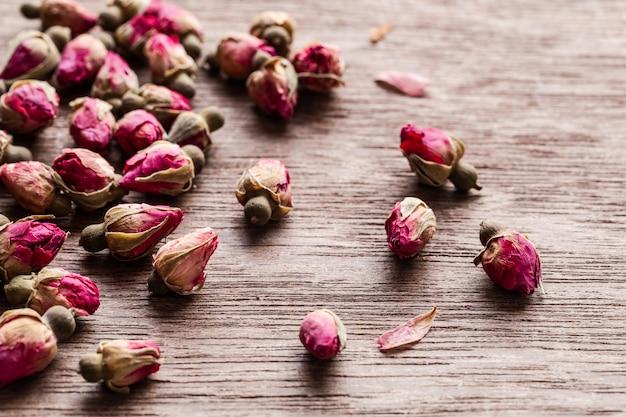 ピンクの赤い乾燥したバラのつぼみは、copyspaceの古い木製のテーブルに散在しています。