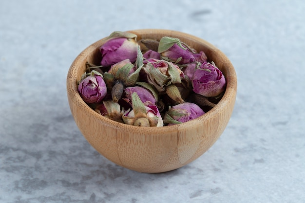 Pink red dried rose buds in a wooden bowl with petals placed on a stone .
