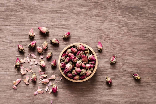 Pink red dried rose buds in wooden bowl with petals
