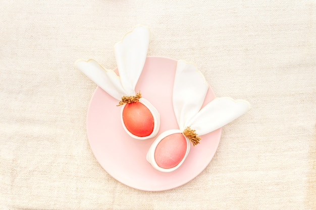 Pink and red eggs with bunny ears on a plate