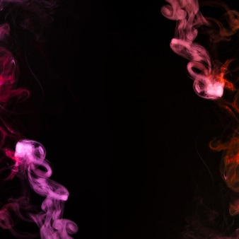 Pink and red plume of smoke becoming wavy swirls on black background