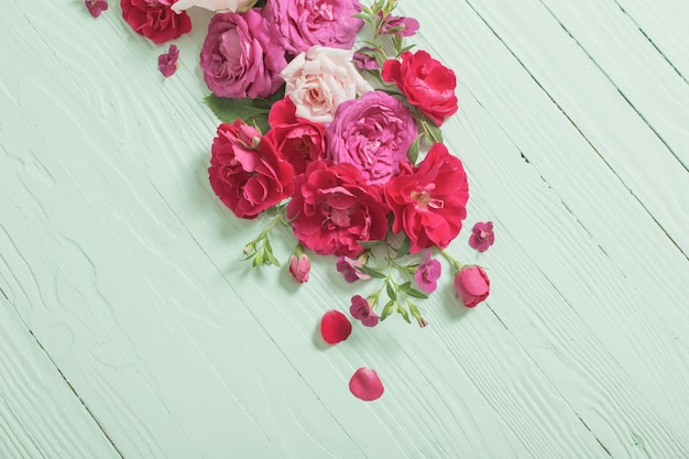 Pink and red roses on green wooden background