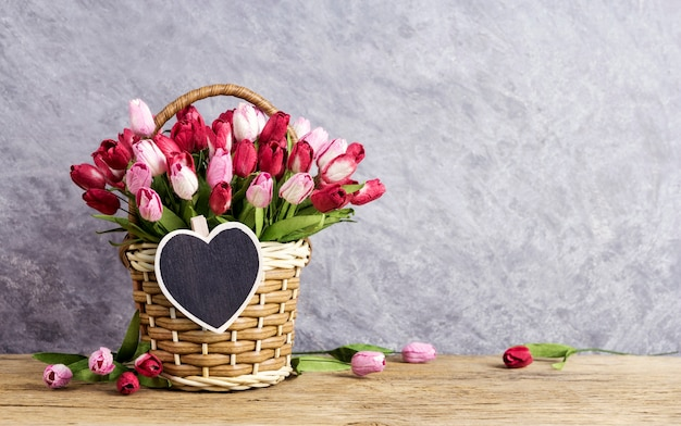 Pink and red tulip flowers in wood basket with blank wood heart