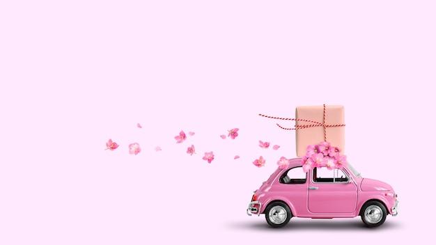 Розовый ретро автомобиль с подарочной коробкой на крыше с цветами на розовом фоне.