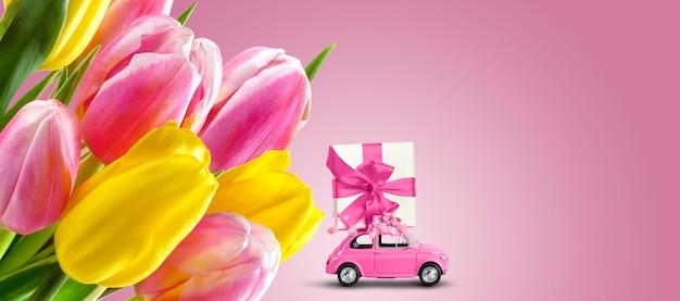 ピンクの背景にチューリップの花と屋根の上のギフトボックスとピンクのレトロな車。グリーティングカード、バナーデザインテンプレート