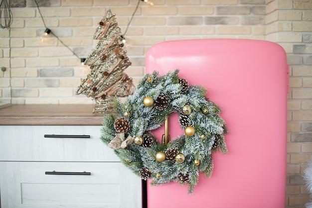 クリスマスリースとピンクのレトロな冷蔵庫