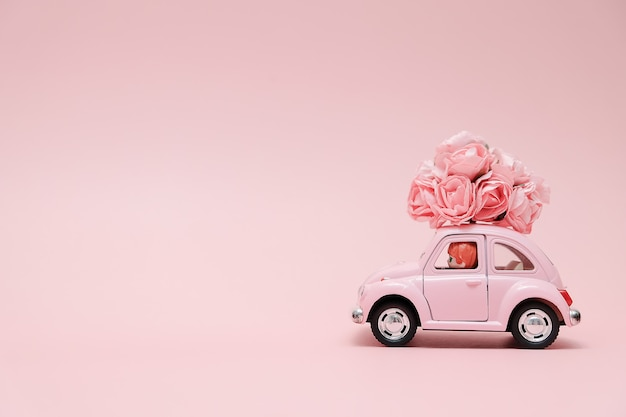 Pink retro toy car delivering bouquet of flowers