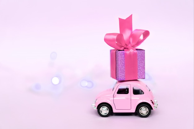Pink retro toy car delivering gift box for valentine's day on pink