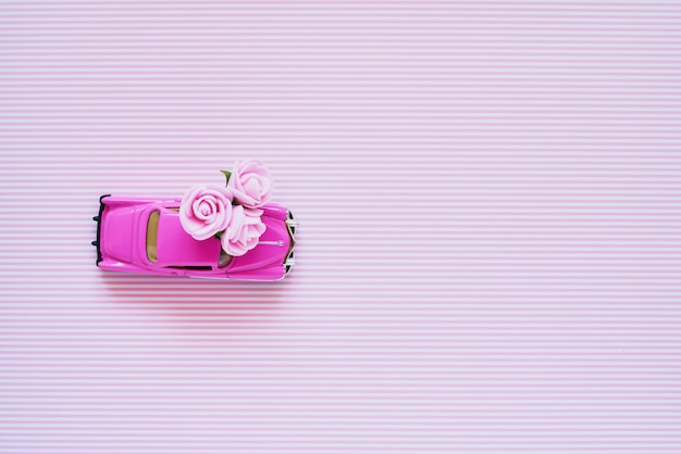 Pink retro toy car delivering pink flowers bouquet on pink background.