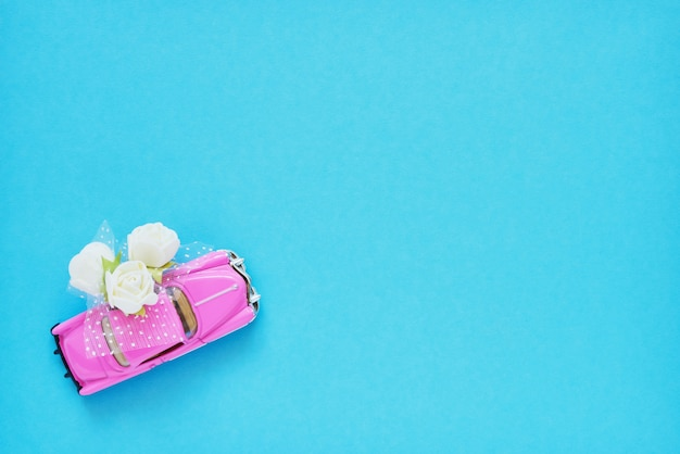 Pink retro toy car delivering white flowers bouquet on blue background.