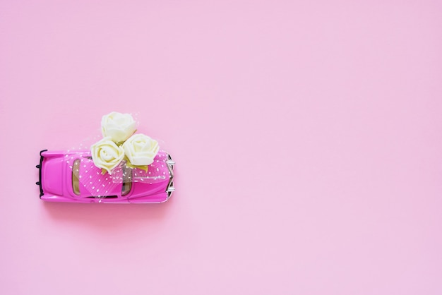 Pink retro toy car delivering white flowers bouquet on pink background.