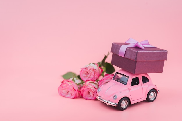 Pink retro toy car delivers a gift box on pink background. february 14 postcard, valentine's day. flower delivery.women's day