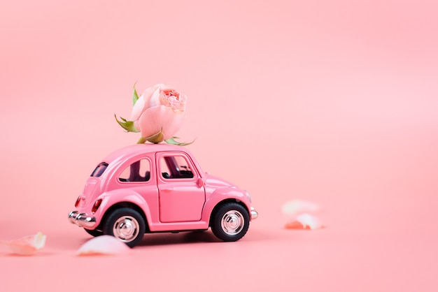 Pink retro toy car delivers a pink flower on pink background. february 14 postcard, valentine's day. march 8, international women's day