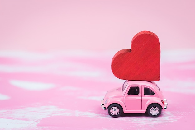 Pink retro toy car delivers a red hart on pink background. february 14 postcard, valentine's day. flower delivery.women's day