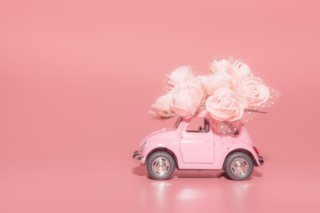 Pink retro toy car with bouquet of white roses on pink