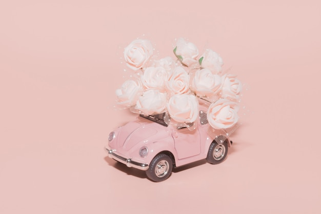 Pink retro toy car with bouquet of white roses on pink.