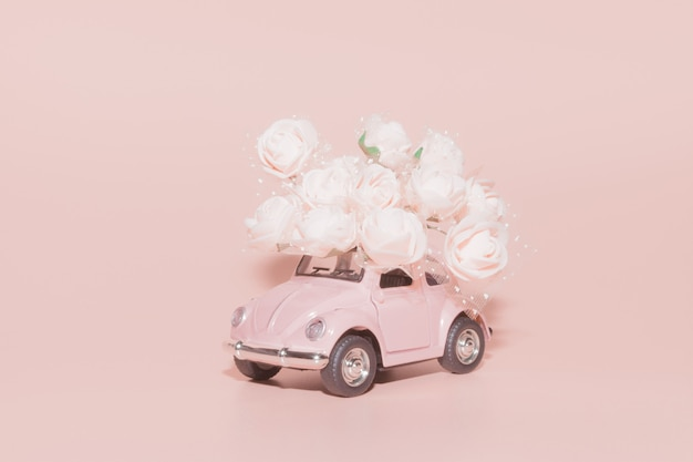Pink retro toy car with bouquet of white