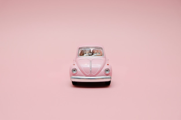 Pink retro toy car with cute couple
