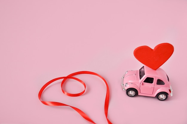 Pink retro toy car with red heart and ribbon