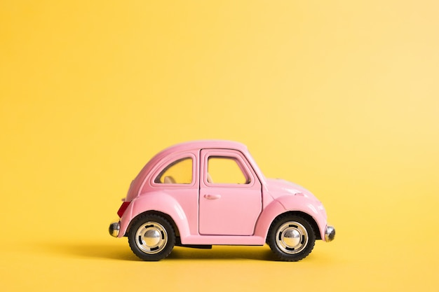 Pink retro toy car on yellow. summer travel concept. taxi.